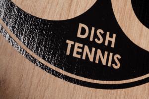 """Nahaufnahme der Oberflächenstruktur mit schwarzem, glänzendem Logo der Natur Holz Mini Tischtennisplatte """"Der kleine Braune"""" mit Maserung"""