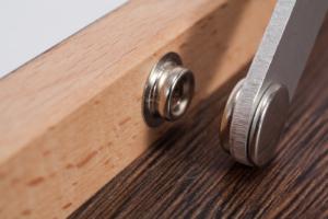 """Nahaufnahme vom Metall Druckknopf bei der Miniplatte """"Die Starke Eiche"""" mit Holzmaserung im Detail."""