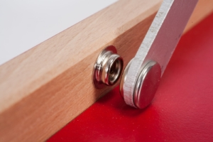 "Closeup of metal push button inside the  wooden frame of Mini ping-pong table red ""The hot chili"""