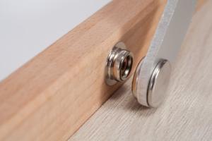 """Nahaufnahme vom Metall Druckknopf bei der Miniplatte """"Das Helle Köpfchen"""" mit Holzmaserung im Detail."""