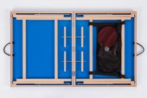 Nahaufnahme eines offenen, blauen Mini Tischtennis Koffer . Die Farbe ist identisch mit der Oberflächenfarbe. Das Netz im Inneren bittet Stauraum für Bälle und Schläger.