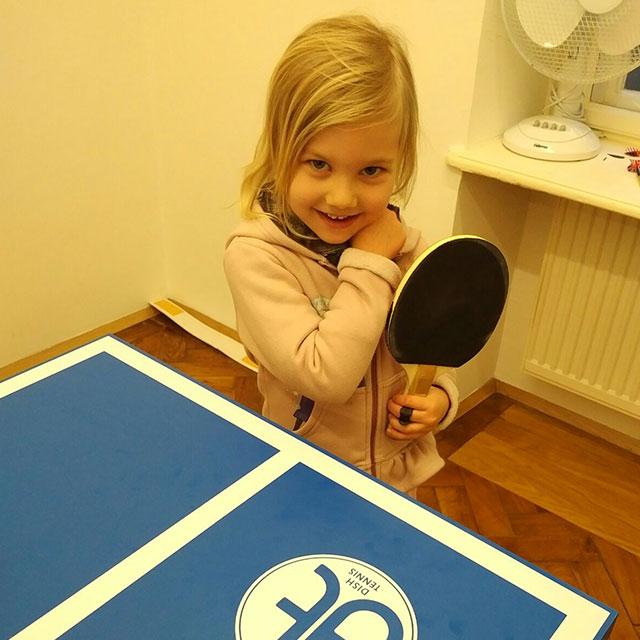 Kleines Mädchen hält zu Hause einen Tischtennis Schläger und steht vor der DIS TENNIS Mini Platte 'Dein Blaues Wunder'